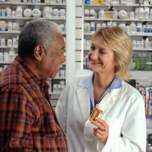 A pharmacist counsels her patient about his prescription medication.