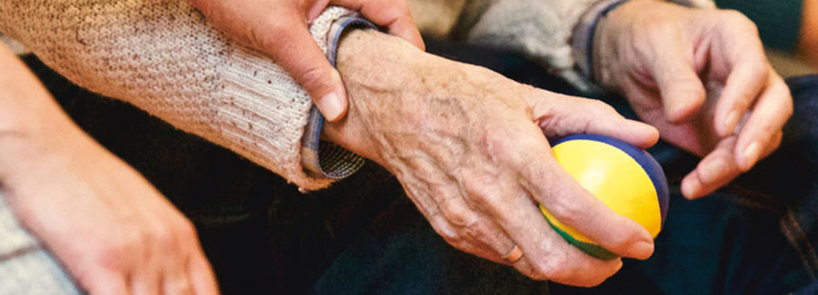 An older person's hand gripping a tennis ball. A caregiver is holding the hand.