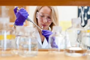 Woman with pipette in lab working on drug development process